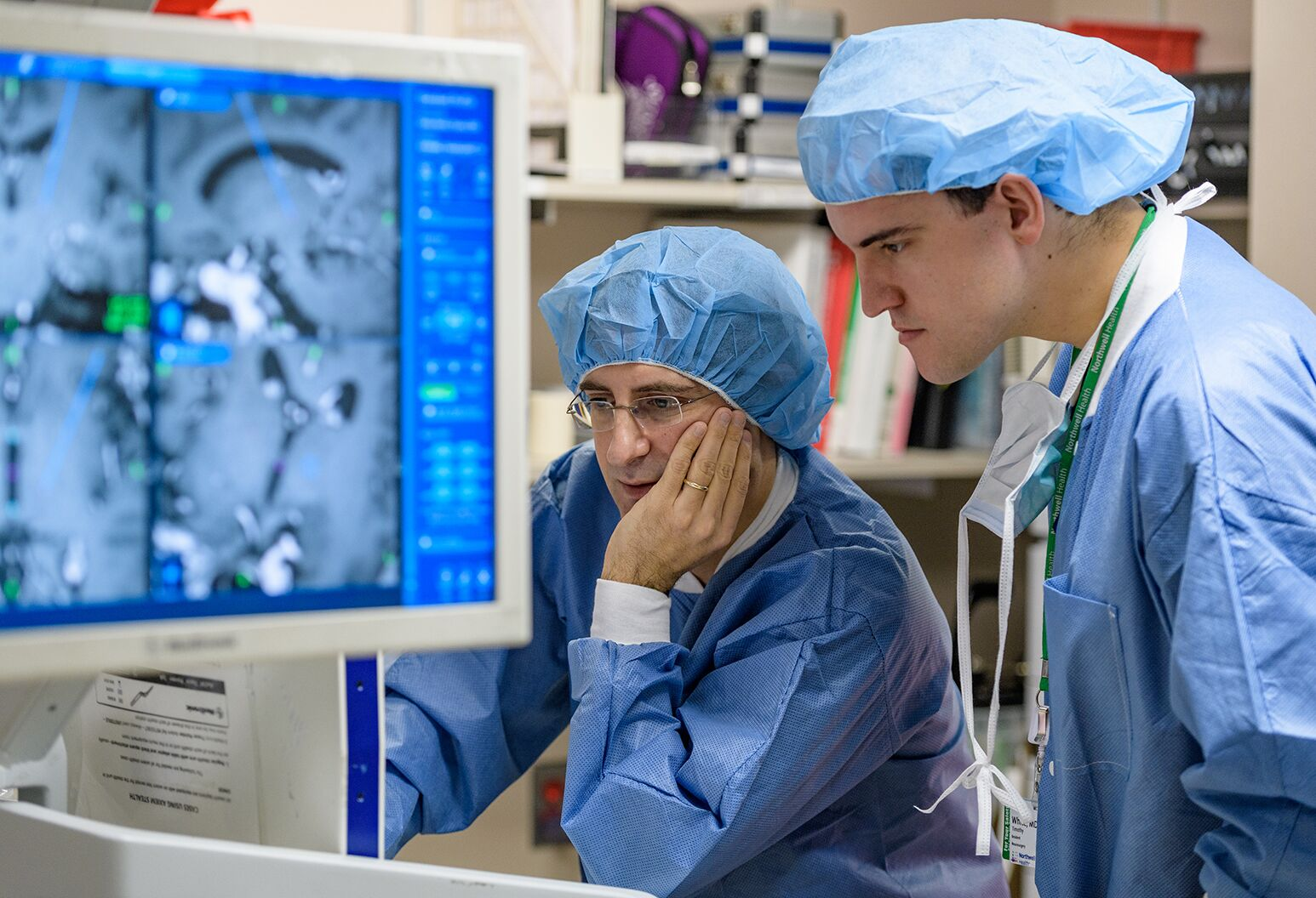 2 people in blue scrubs observing a technical device