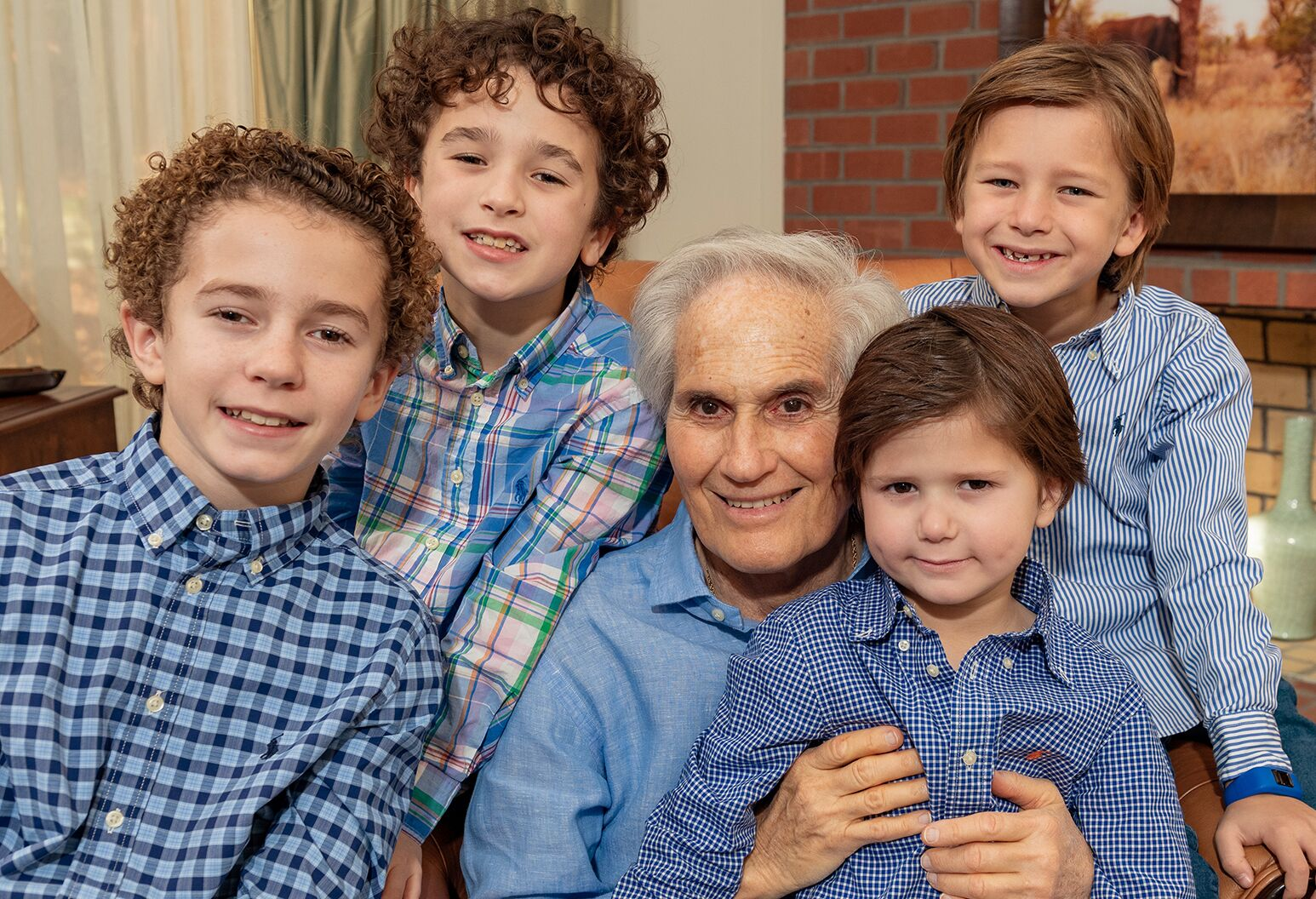 A man in his late 70s poses with his four school-aged grandsons. Everyone is wearing blue.