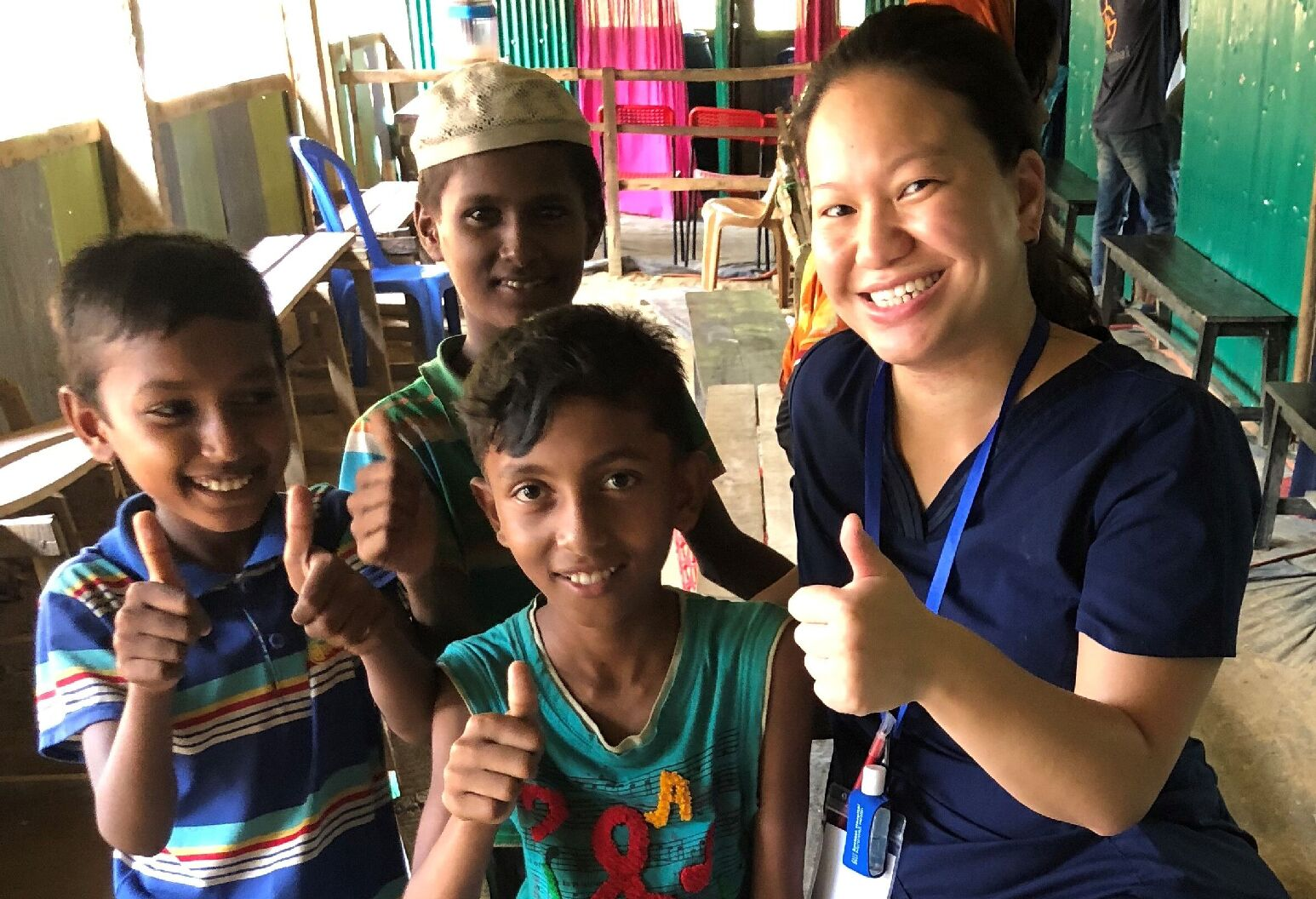 Nina posing with patients giving thumbs up