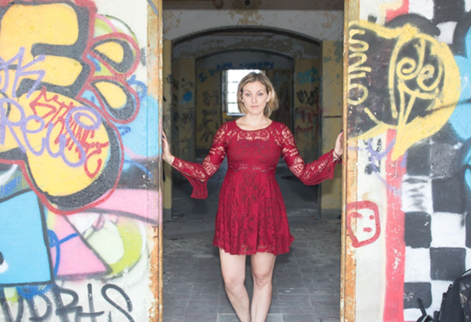 Woman standing in doorway of a building covered in graffiti