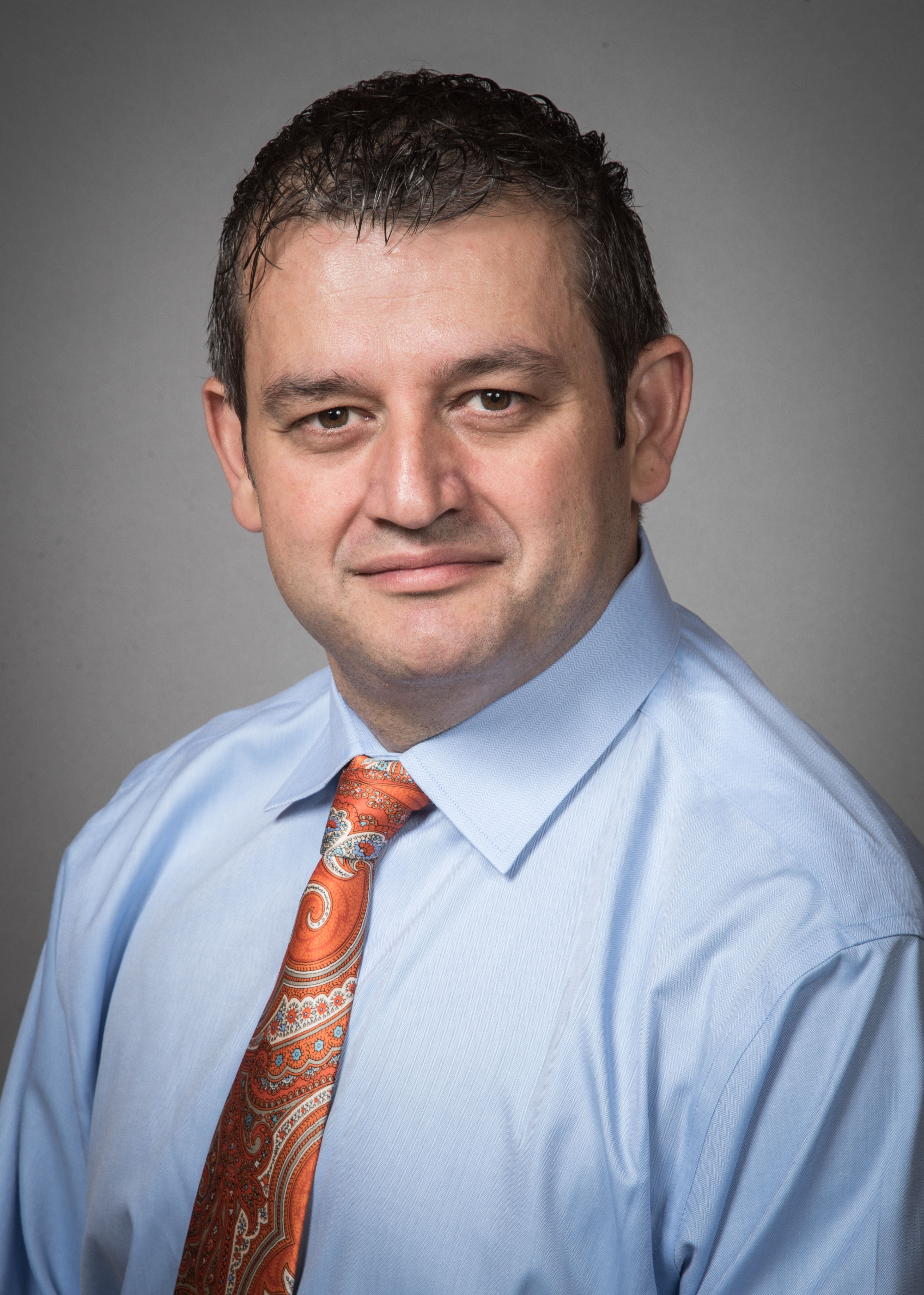 Brahim Ardolic, MD, wearing a blue shirt and orange tie