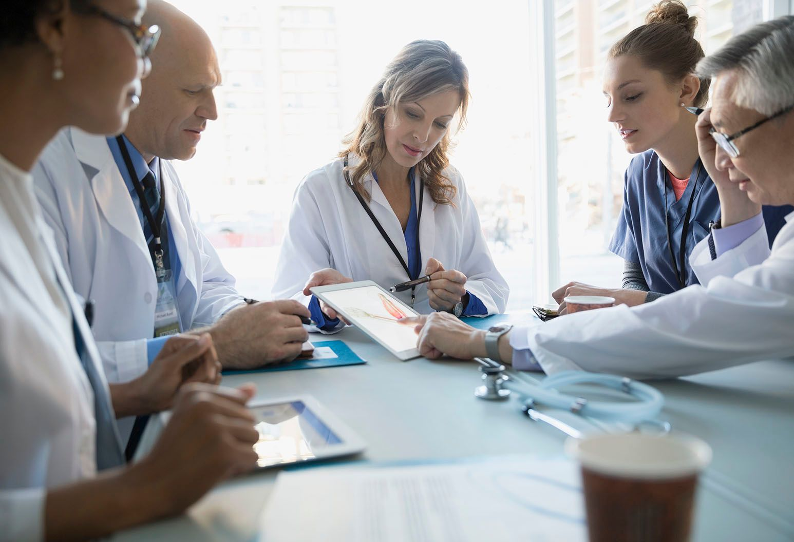 Several doctors, male and female, sit at a table collaborating. A female doctor with blonde hair has an image on a tablet and another doctor is pointing to it.