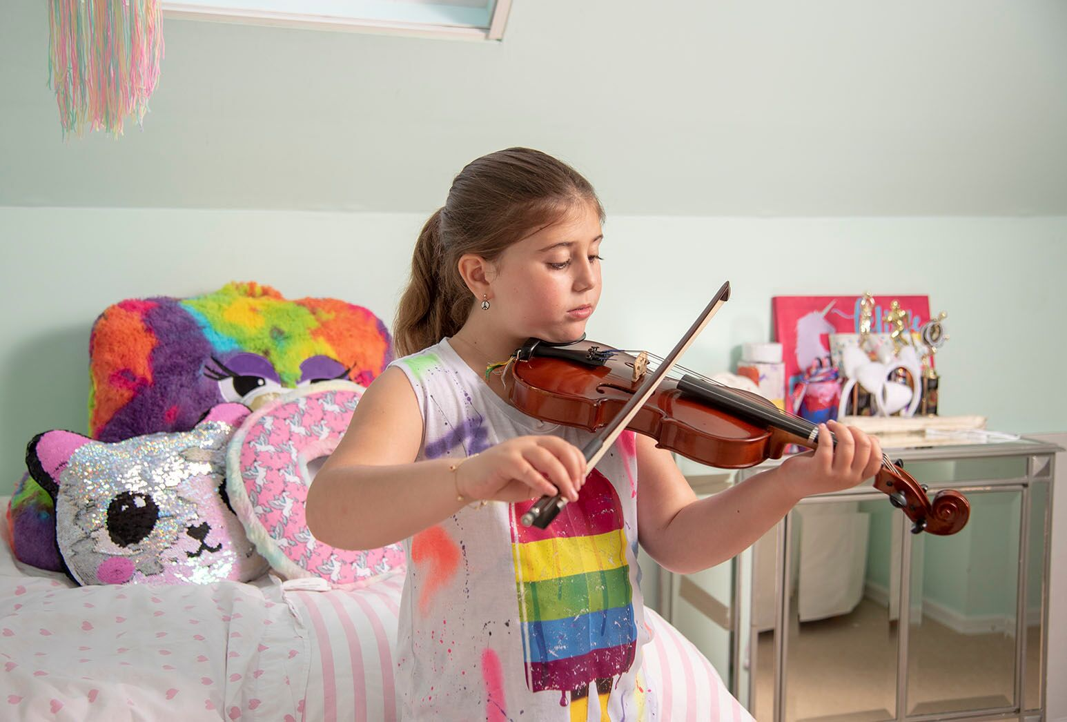 Young girl playing the viola next to her bed.