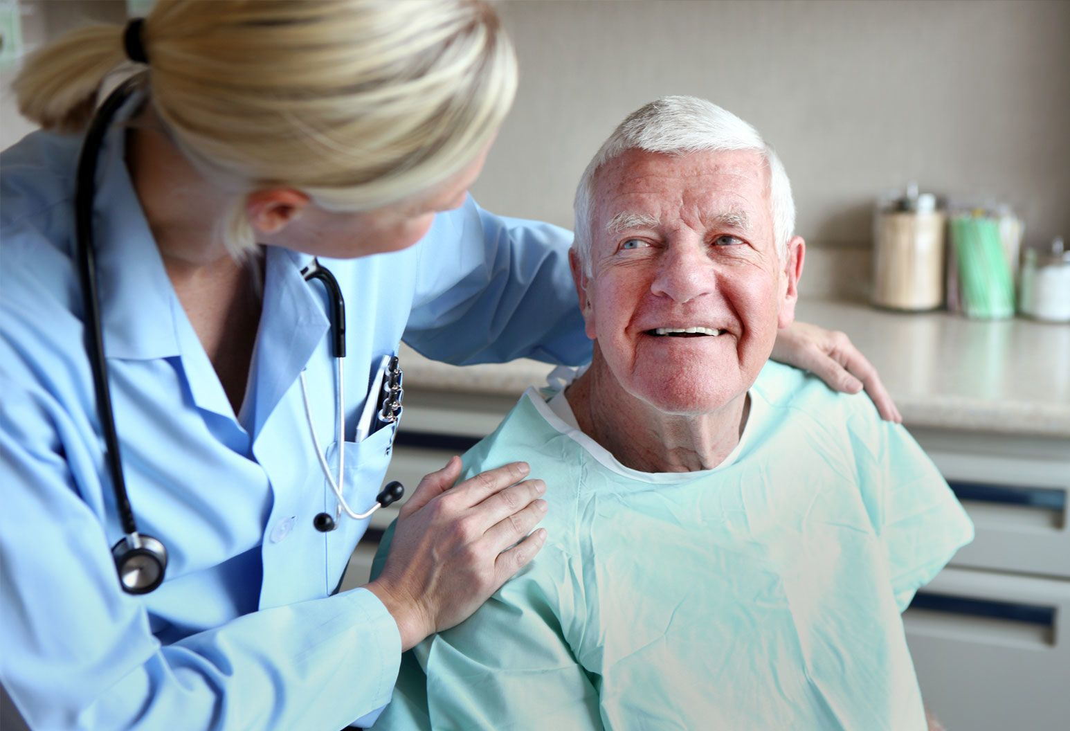 Blonde female doctor with stethoscope around her neck gently holds shoulders of smiling, older male patient in paper gown