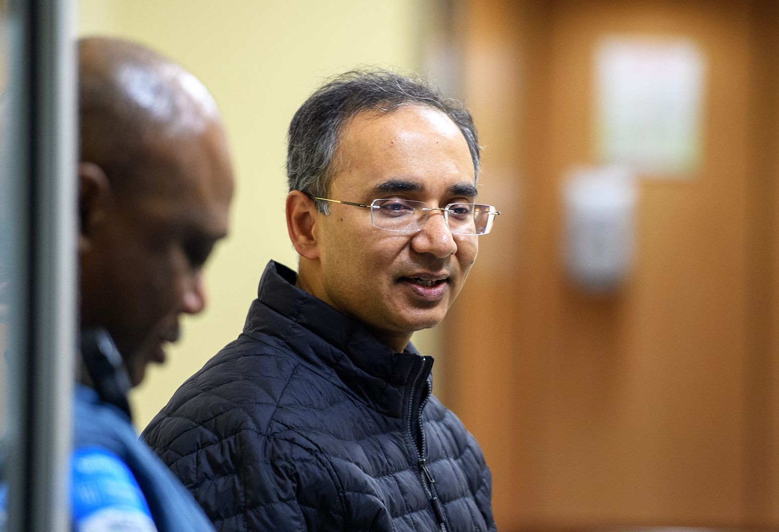 One man is smiling and wearing glasses and a blue jacket. Another man is half in the frame and also wears a blue jacket.