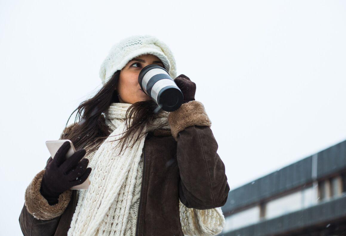 Woman drinking from travel mug