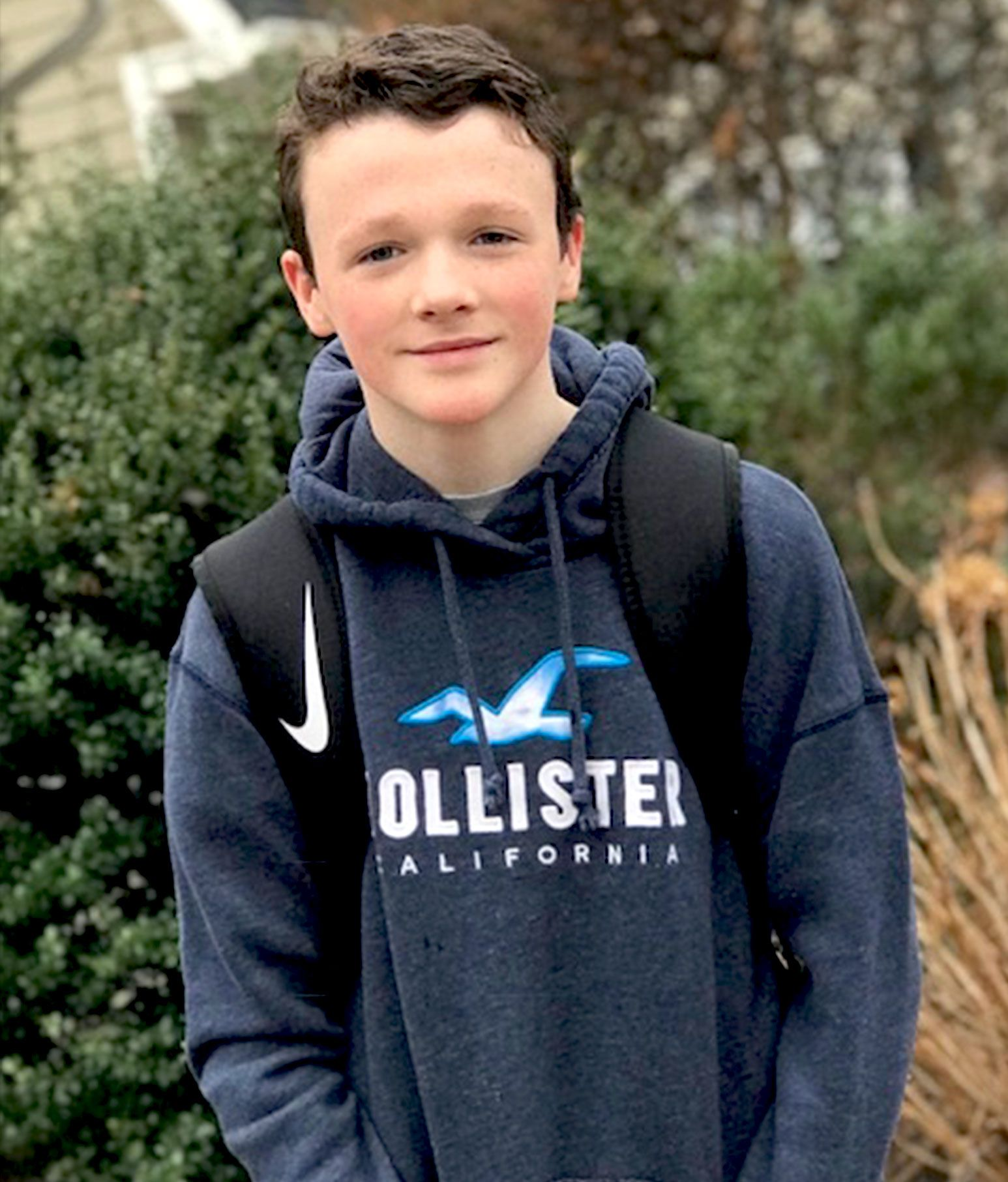 A teenage boy in a grey Hollister hoodie and bookbag smiles for the camera.