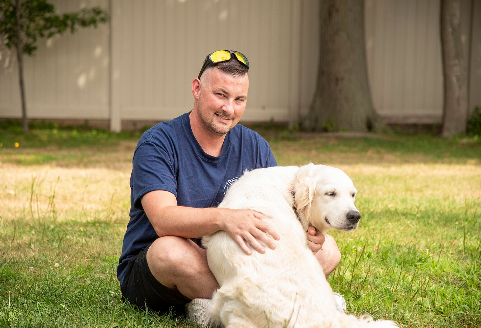 A man with sunglasses on his head sits on the grass with a large white dog.