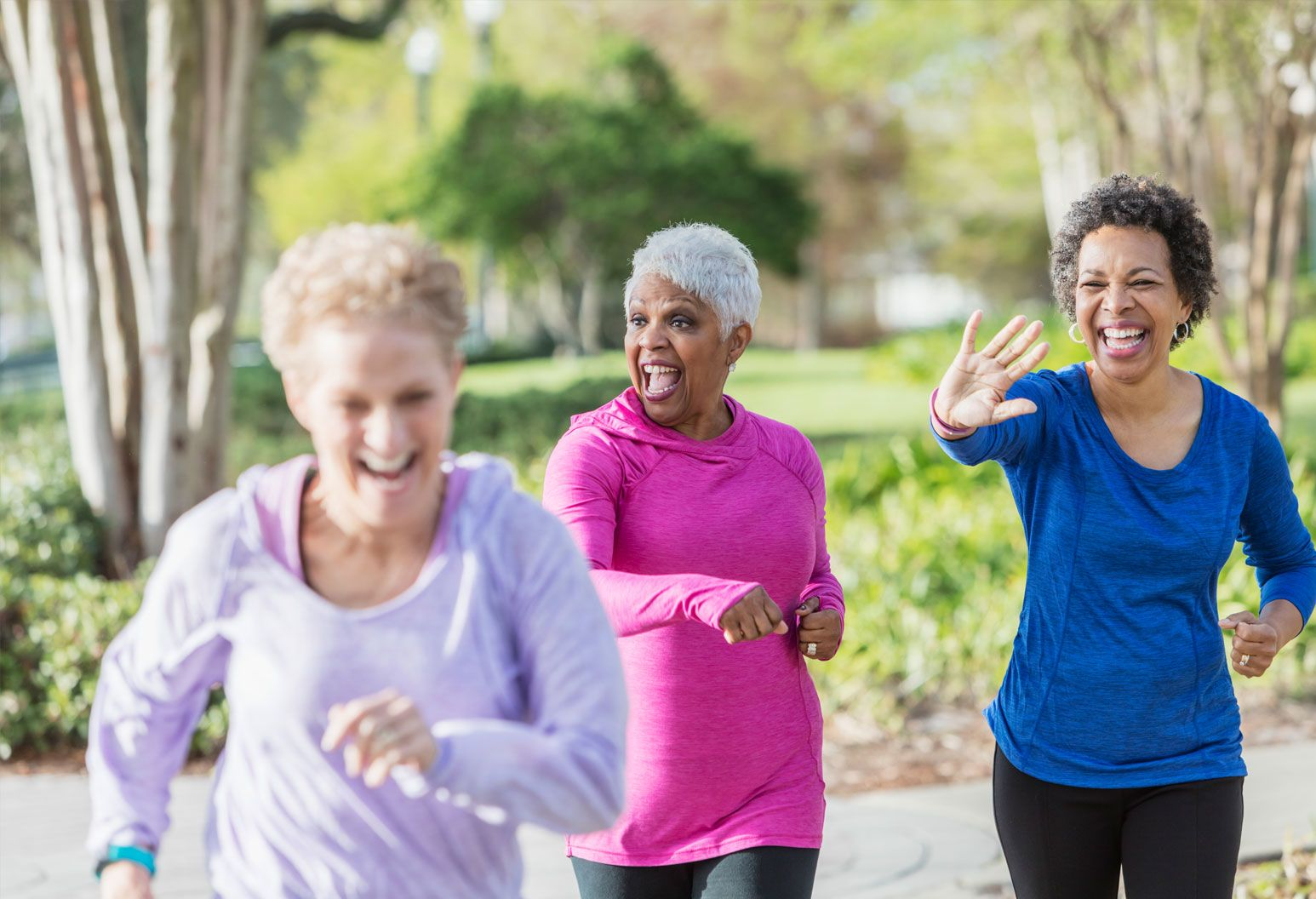 A group of three women exercise outside with big smiles on their faces.
