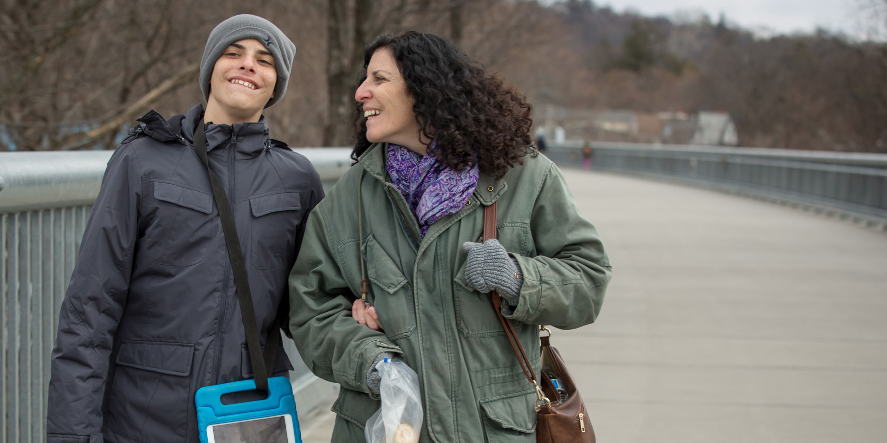 A boy in a grey hat and jacket walks arm in arm with a woman in a green jacket and purple scarf. The woman has dark curly hair and is smiling at the boy who looks straight ahead.