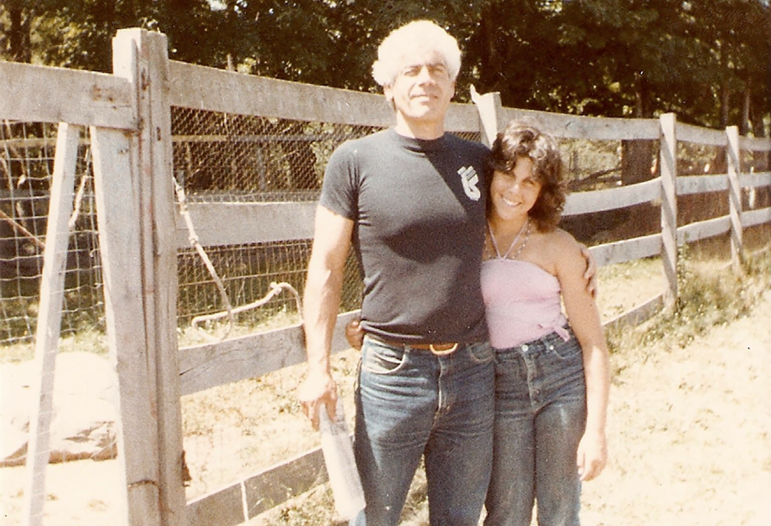 Very fit older man with white hair stands tall in a tight fitting black t-shirt and jeans. Also posing with him is a younger woman in jeans and a pink blouse. They are both smiling as they stand in front of a wooden fence out doors.