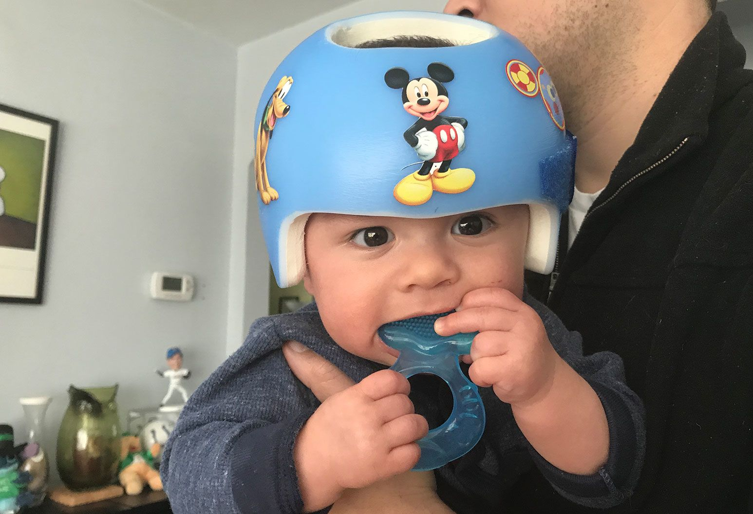 A baby wearing a blue helmet with Disney character stickers on it chews on a teething toy while being held by an older man.