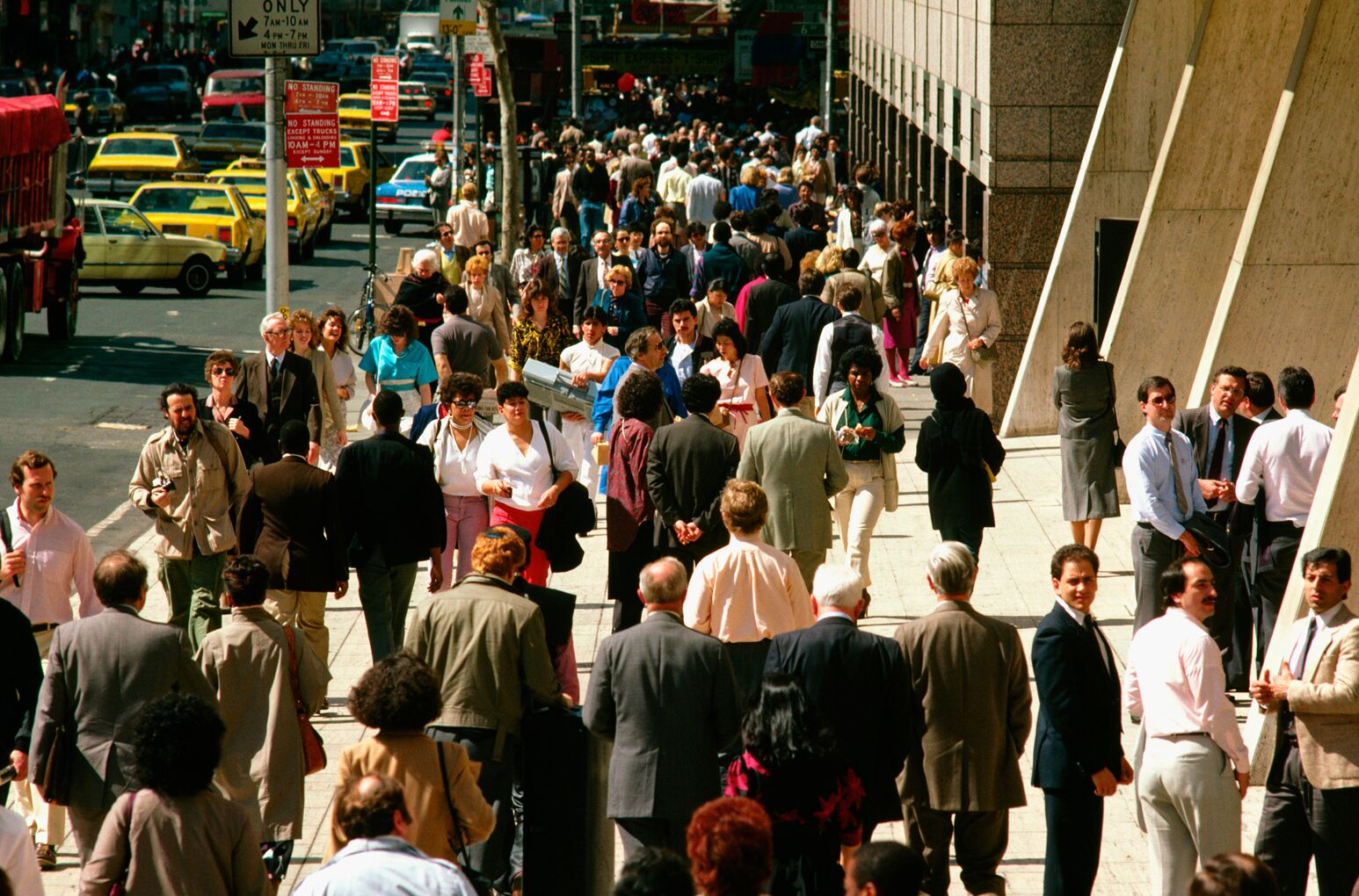 A population of people walk on a busy city street
