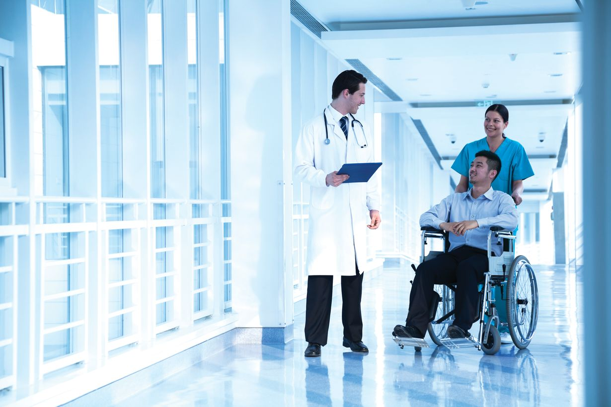 Male doctor walking in the hospital hallway with a male patient being wheeled by a female nurse practitioner.