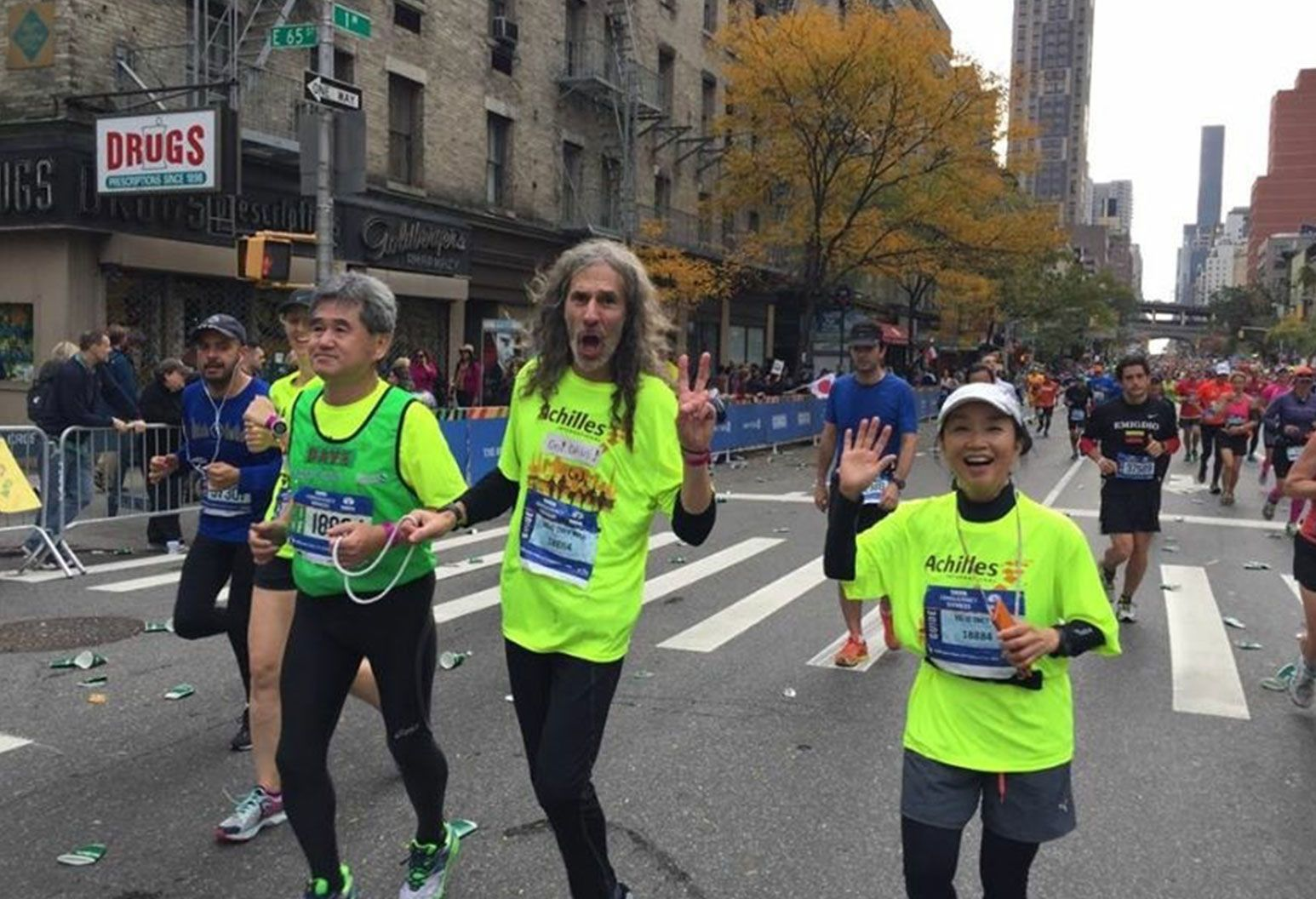 A trio of people running in the street during a marathon pose for the camera. They are all wearing neon green shirts. The man on the far left has grey hair and looks straight ahead, the man in the middle with long hair raises a peace sign, and the woman on the right waves at the camera.