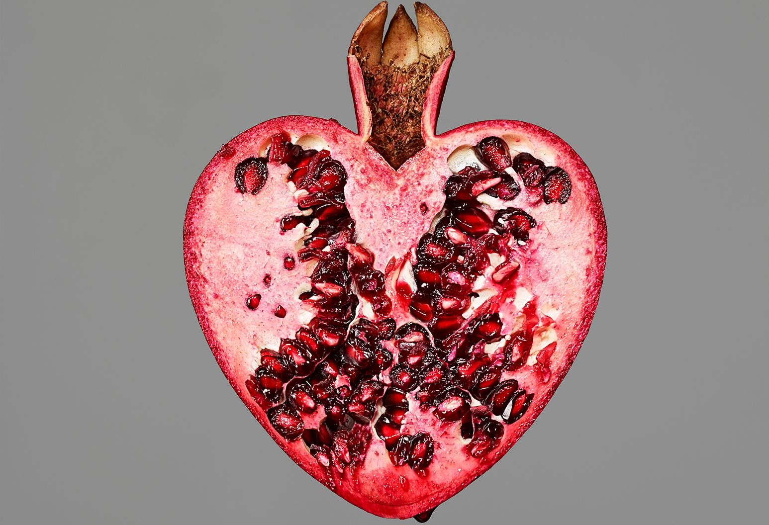 A heart shaped pomegranate is cut in half.