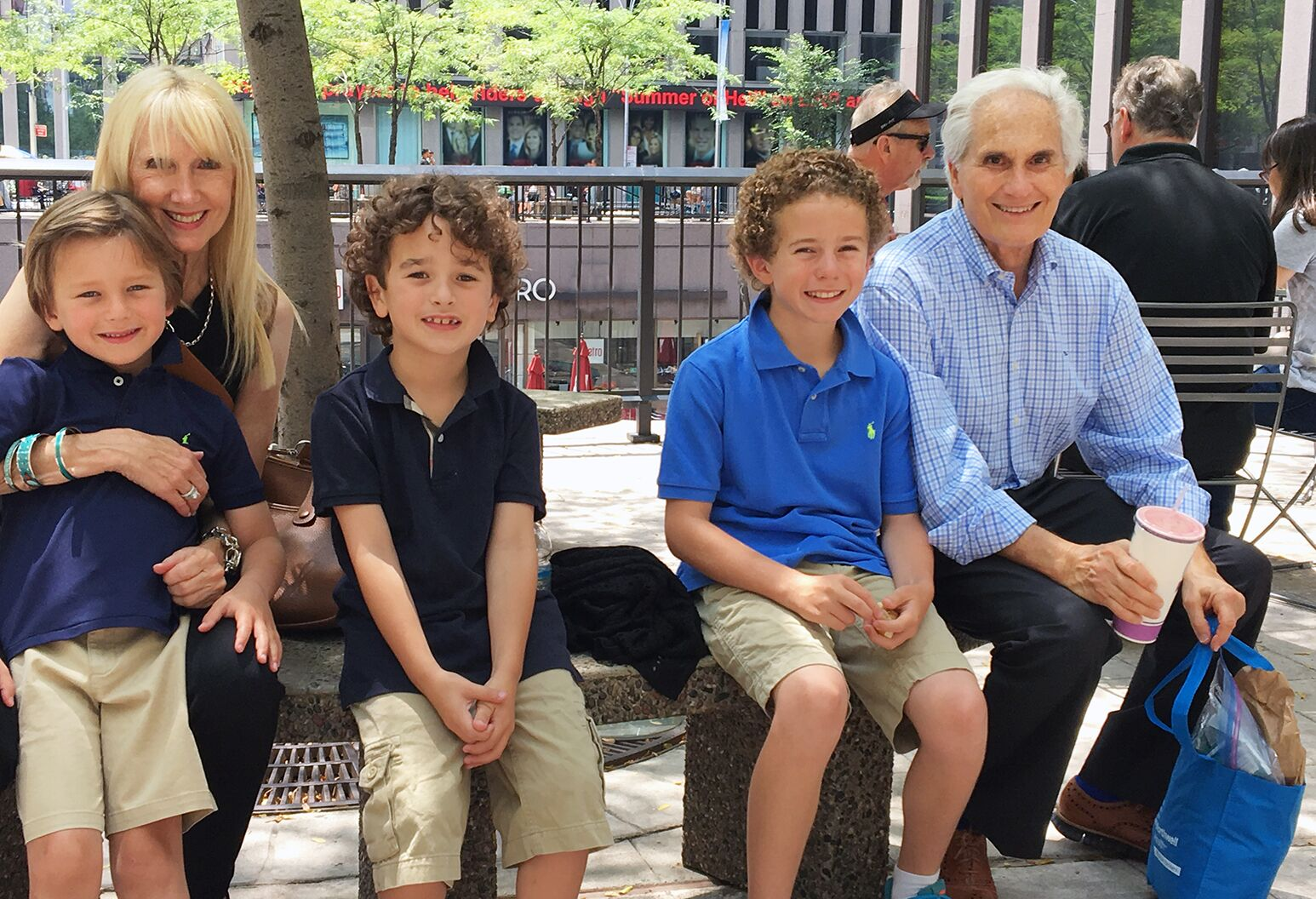 A man and woman in their 70s sit on a bench outside with their three grandsons.