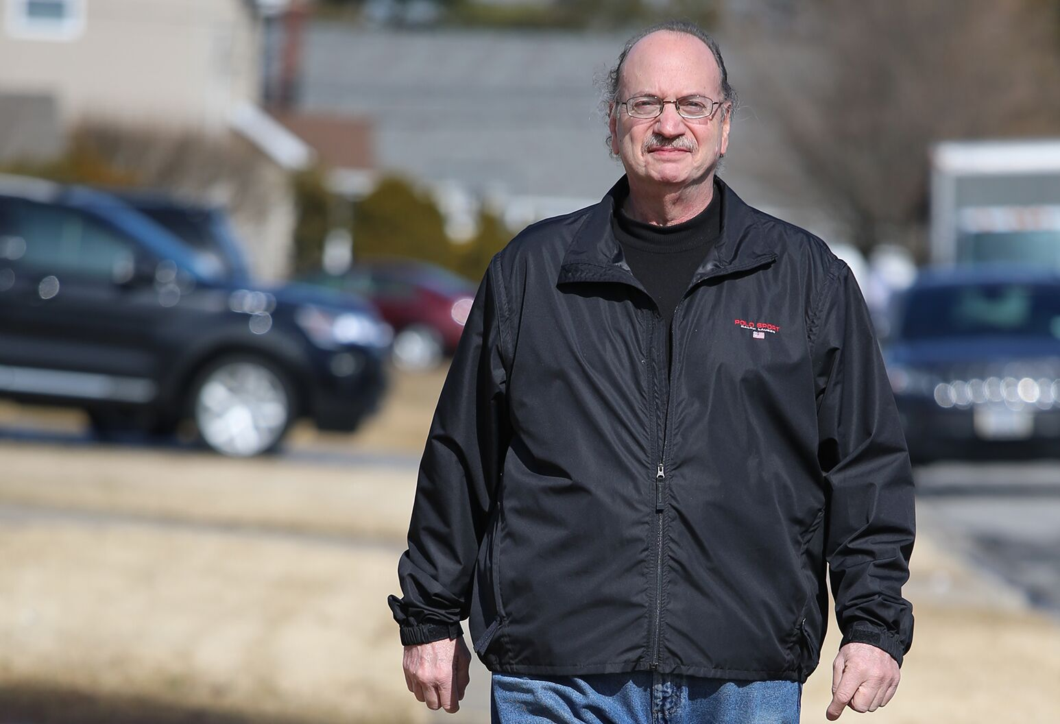 Man in his 60s walks through residential neighborhood.