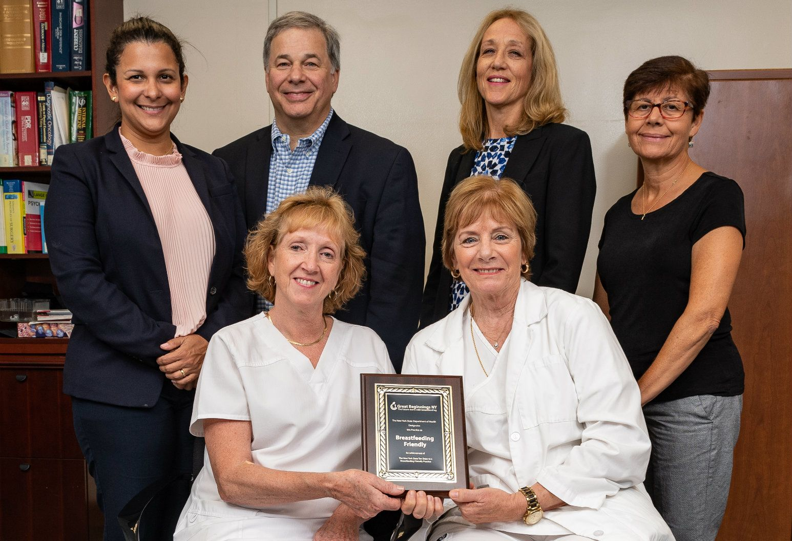 Mary Goussis, RN, and other staff hold a plaque designating Glen Cove Family Medicine as a breastfeeding friendly facility.