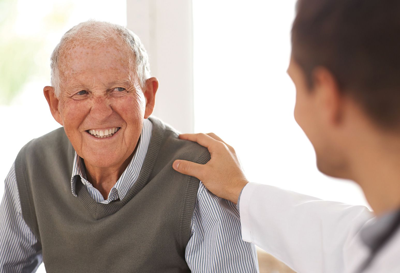 Elderly man wearing a blue shirt and grey sweater is smiling talking to a doctor who has his hand on the man's shoulder
