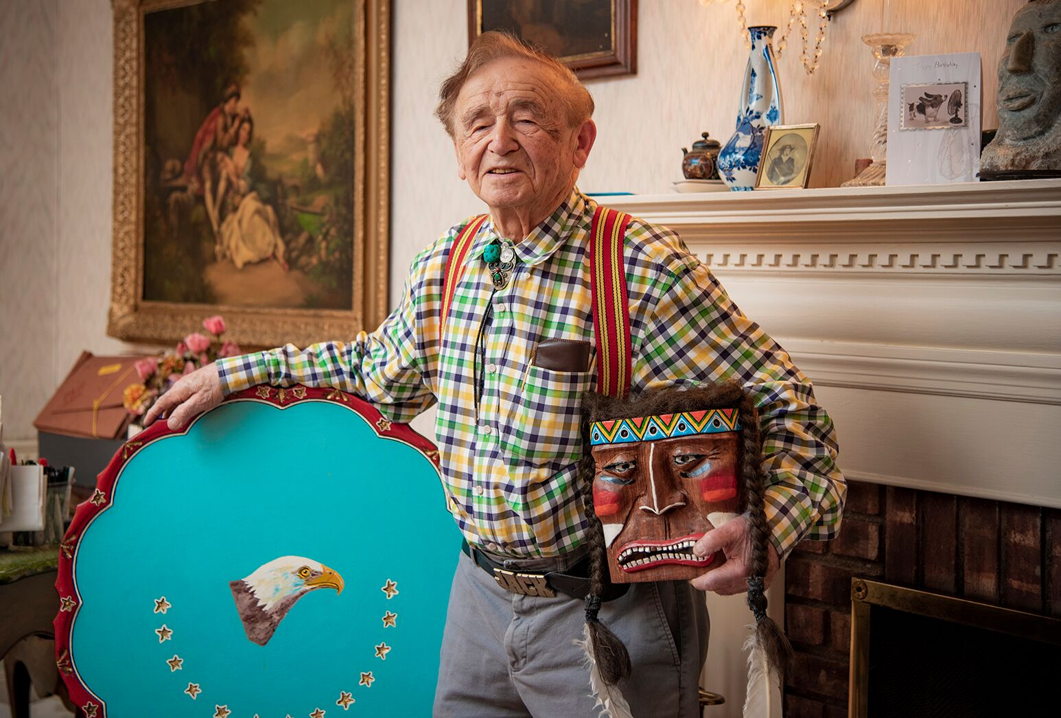 Man in his home poses with colorful art.