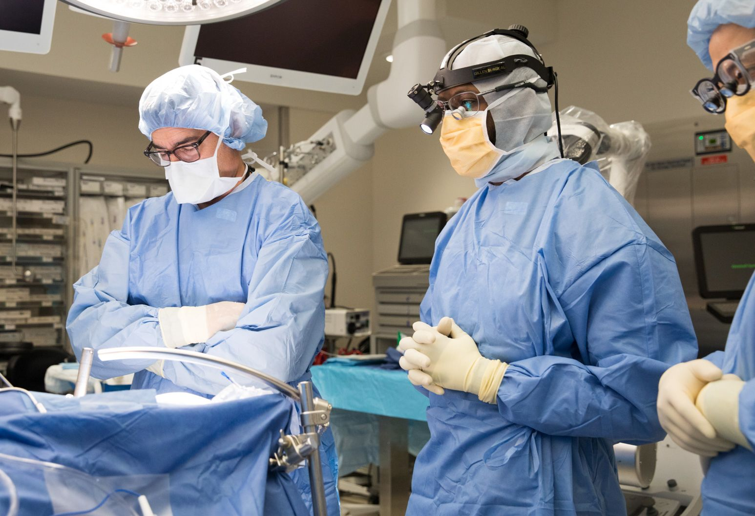 A team of doctors dressed in blue scrubs prepare for surgery in an operating room. Bright lights are overhead and a surgical table is in the middle of the room.