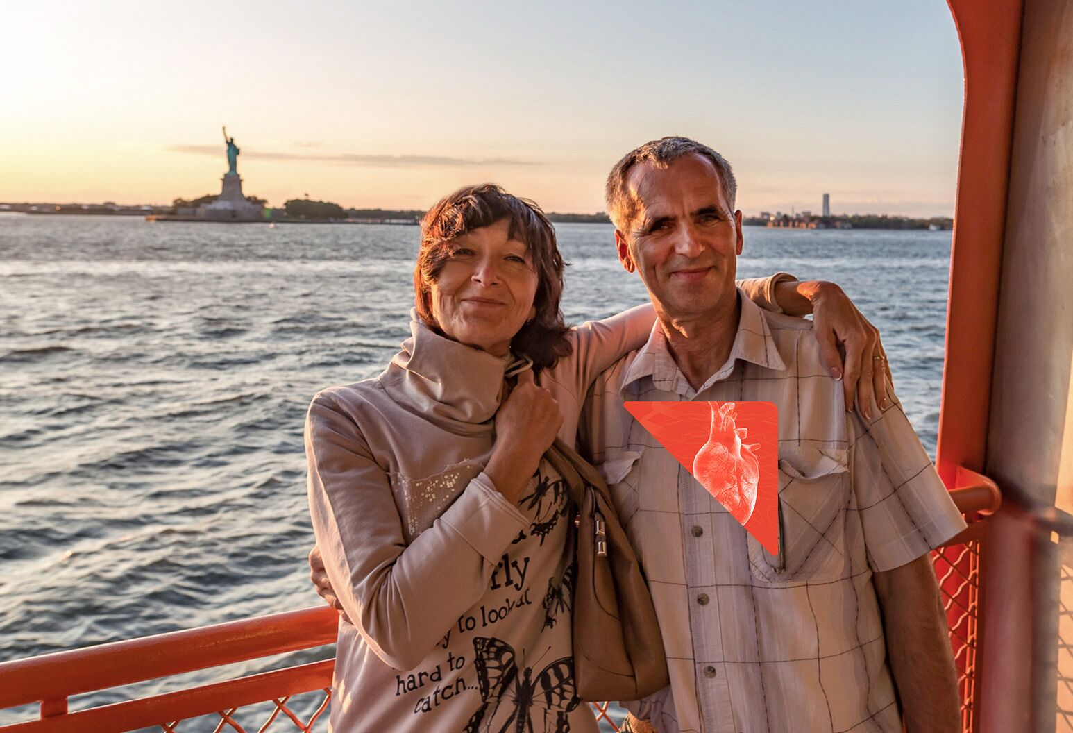 Woman with arm around man, standing on ferry near statue of liberty