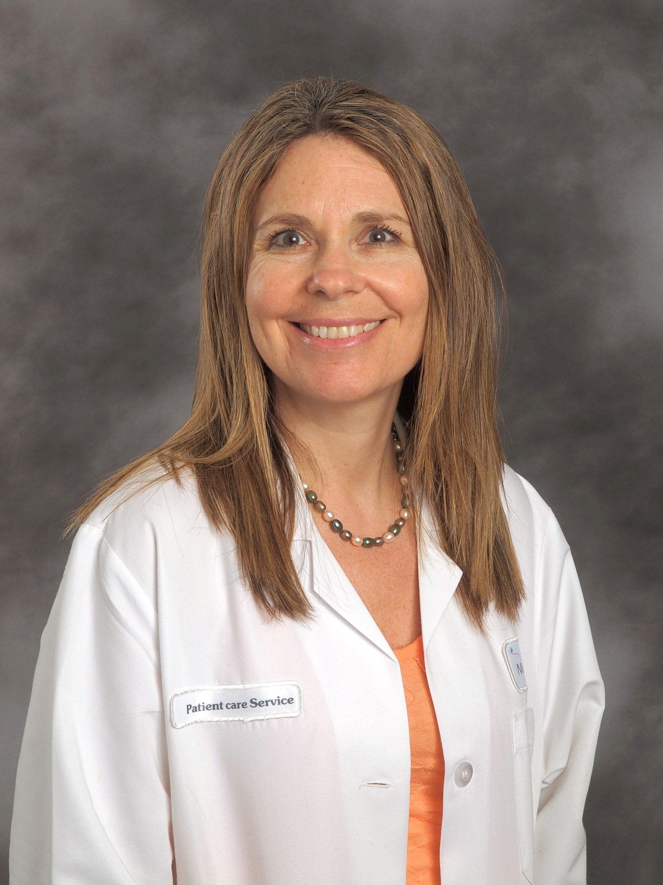Marla Koroly, MD, wearing an orange shirt