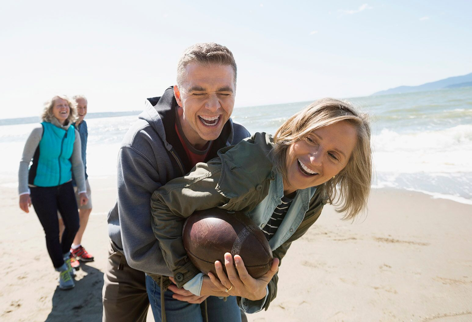 A middle aged couple pictured on a beach, wrestling over a football.
