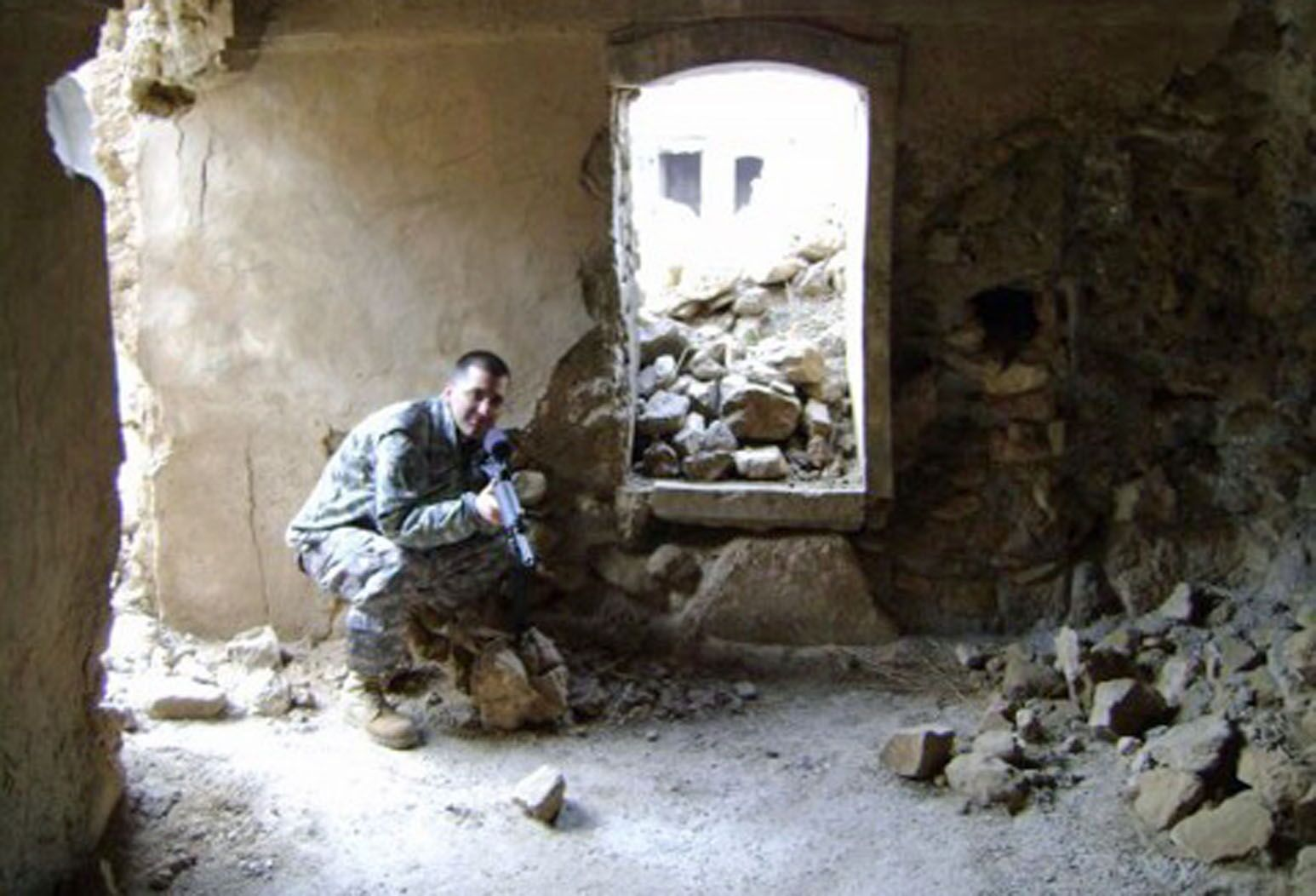 Omar Bholat, MD, holds a machine gun while crouching in a crumbled building in Iraq