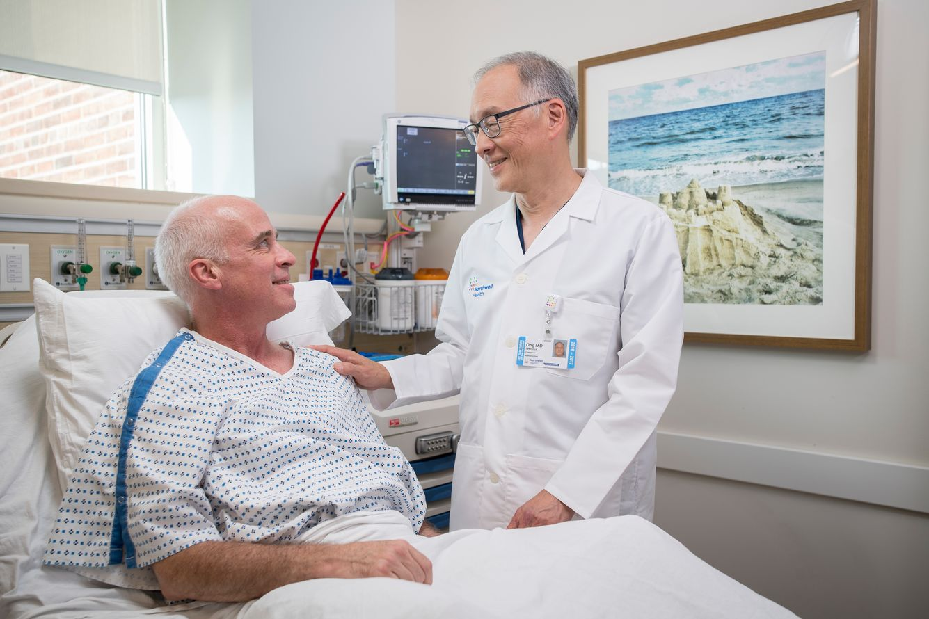 Male patient in hospital bed looking at standing male physician. The doctor has his hand on patient's shoulder and the two smile and look at each other.