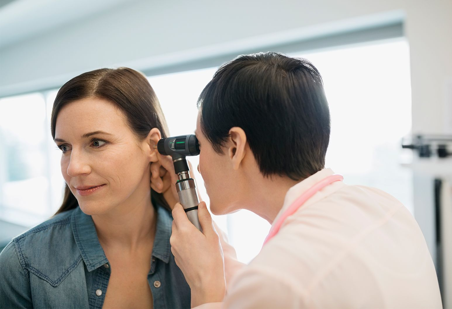 female physician checking the ear of a patient with otoscope