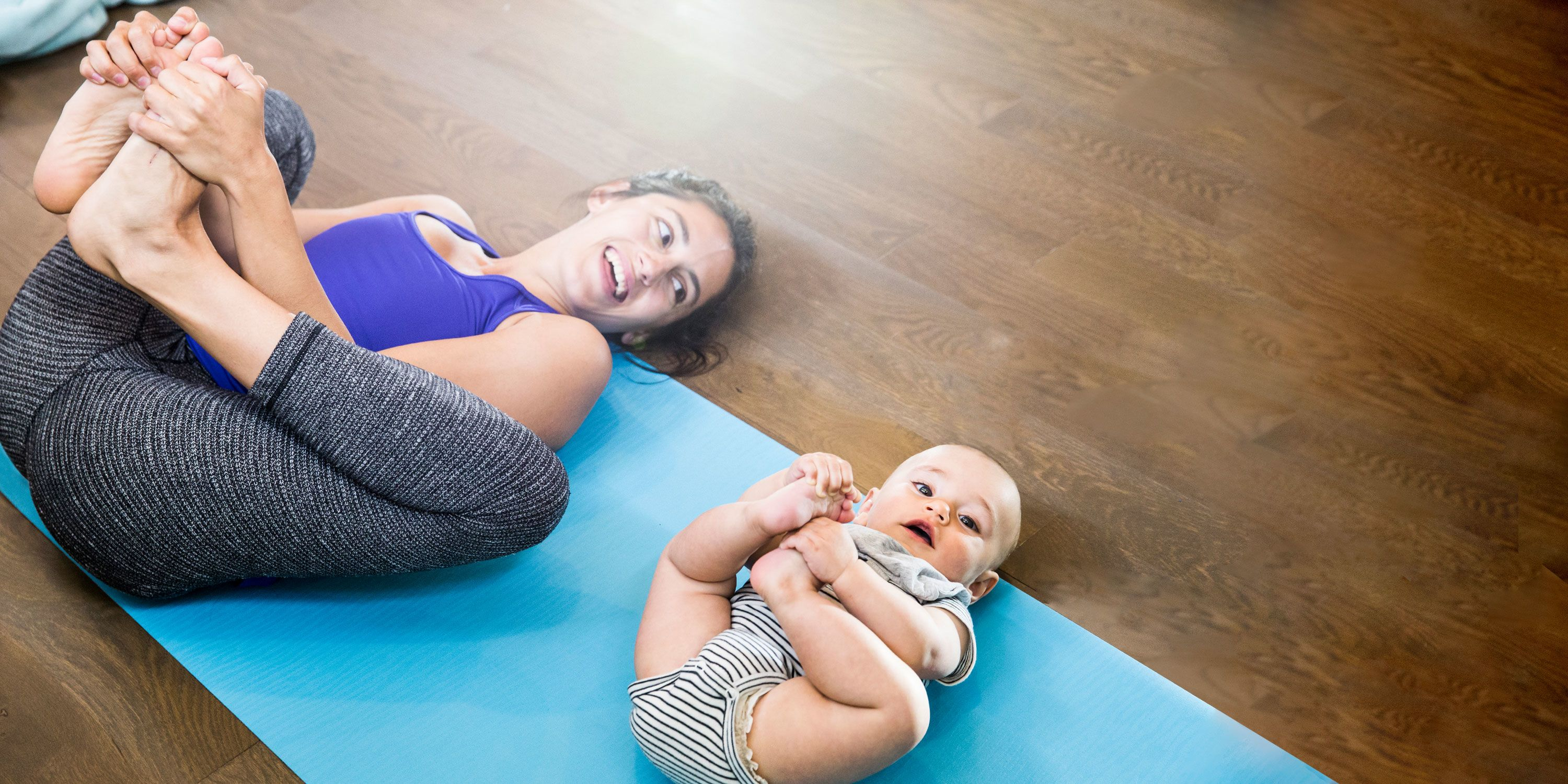 A woman in aerobic clothing lays down on a yoga mat grabbing her toes together. She smiles at a baby laying next to her performing the same pose.