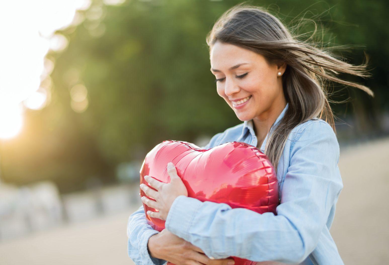 Woman embracing a heart shaped balloon.