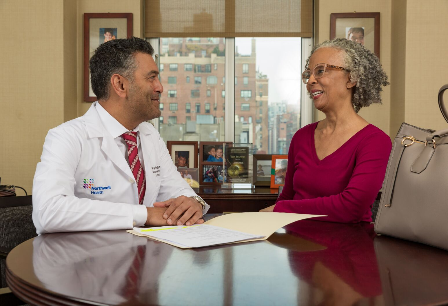 a physician and patient sitting at a table smiling at each other while going over a file on the table