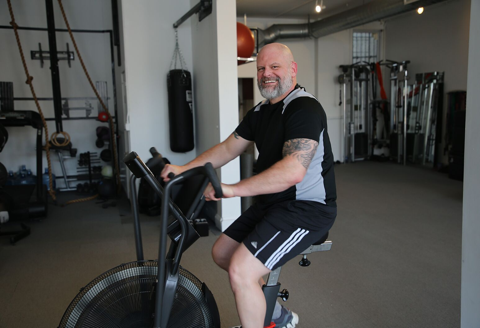 Smiling man in his mid-40s with a beard and tattoos, riding a stationary bicycle.