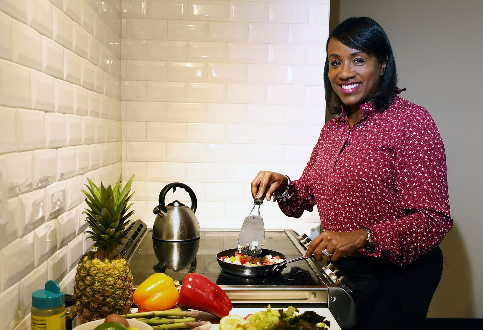 Smiling woman cooks a healthy vegetable stir-fry.