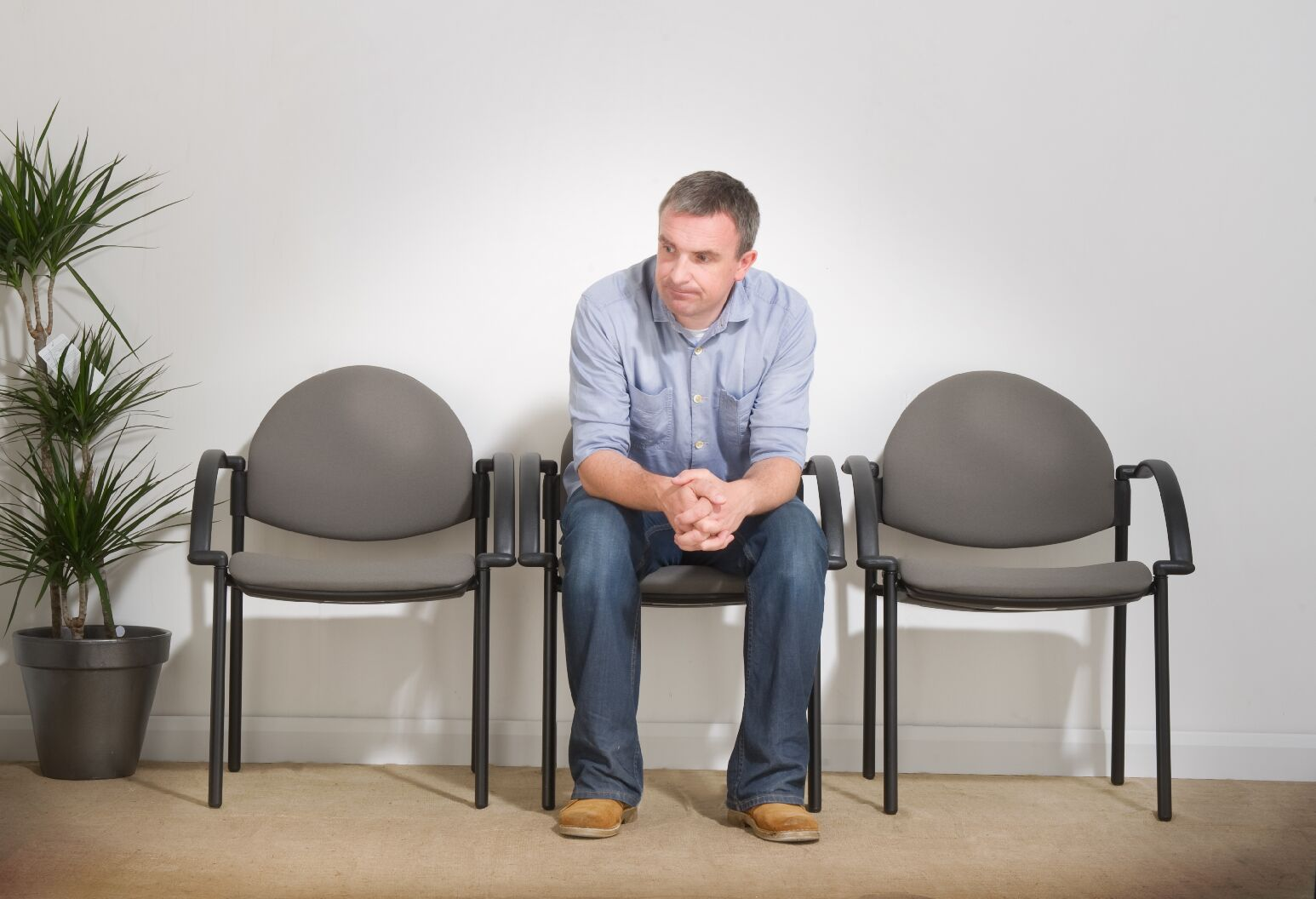 Man sitting alone in a doctors office waiting room.