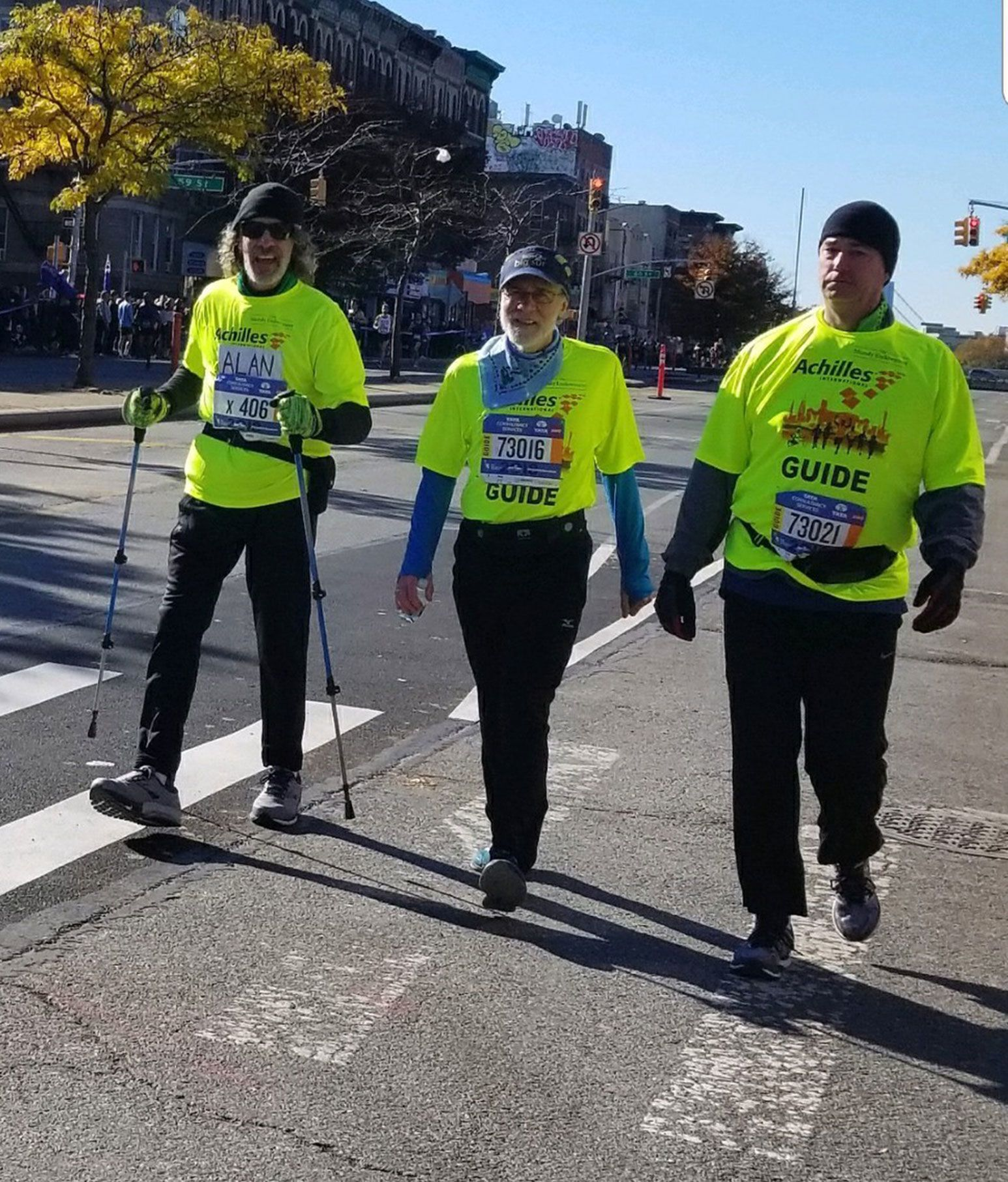 A trio of men are walking down a street together. They all are wearing black pants with neon green shirts. The man on the left is also using walking sticks in both hands.