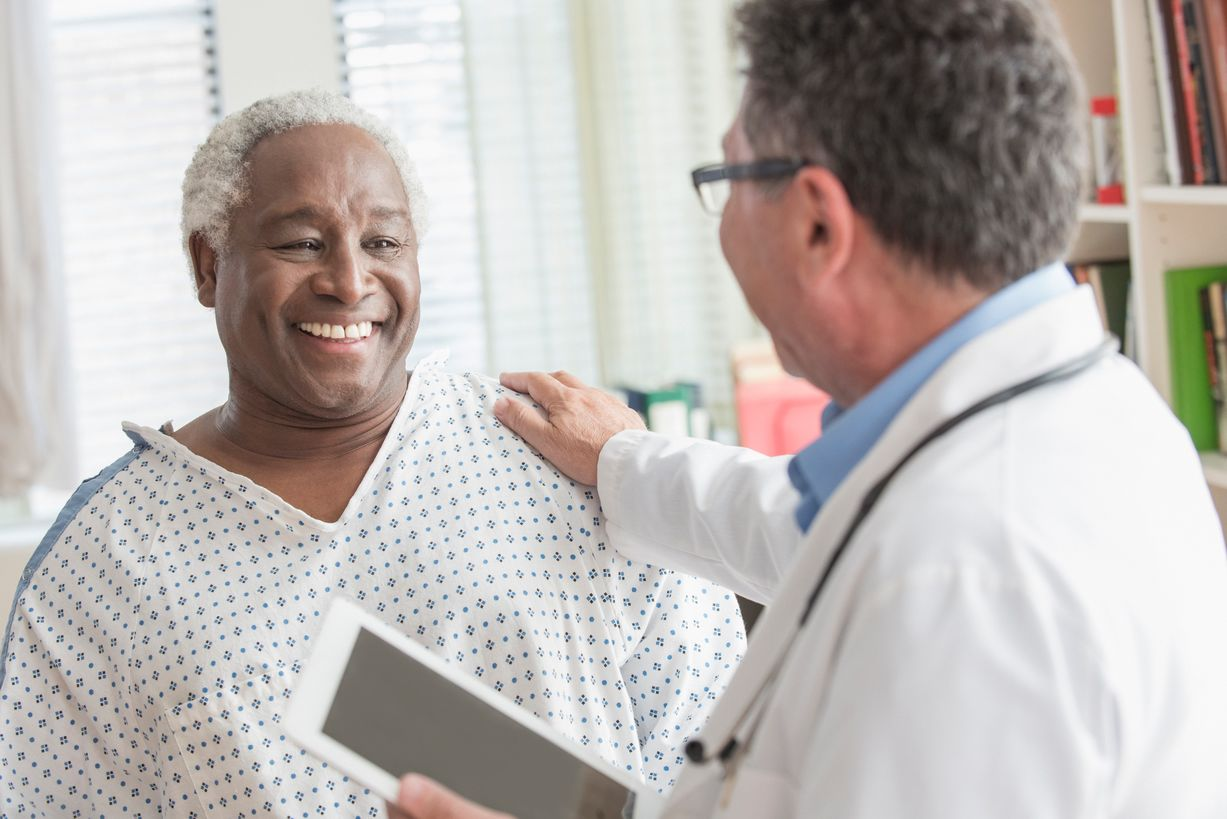 Happy male patient wearing a hospital gown talking to a male doctor who has his hand on the patients shoulder
