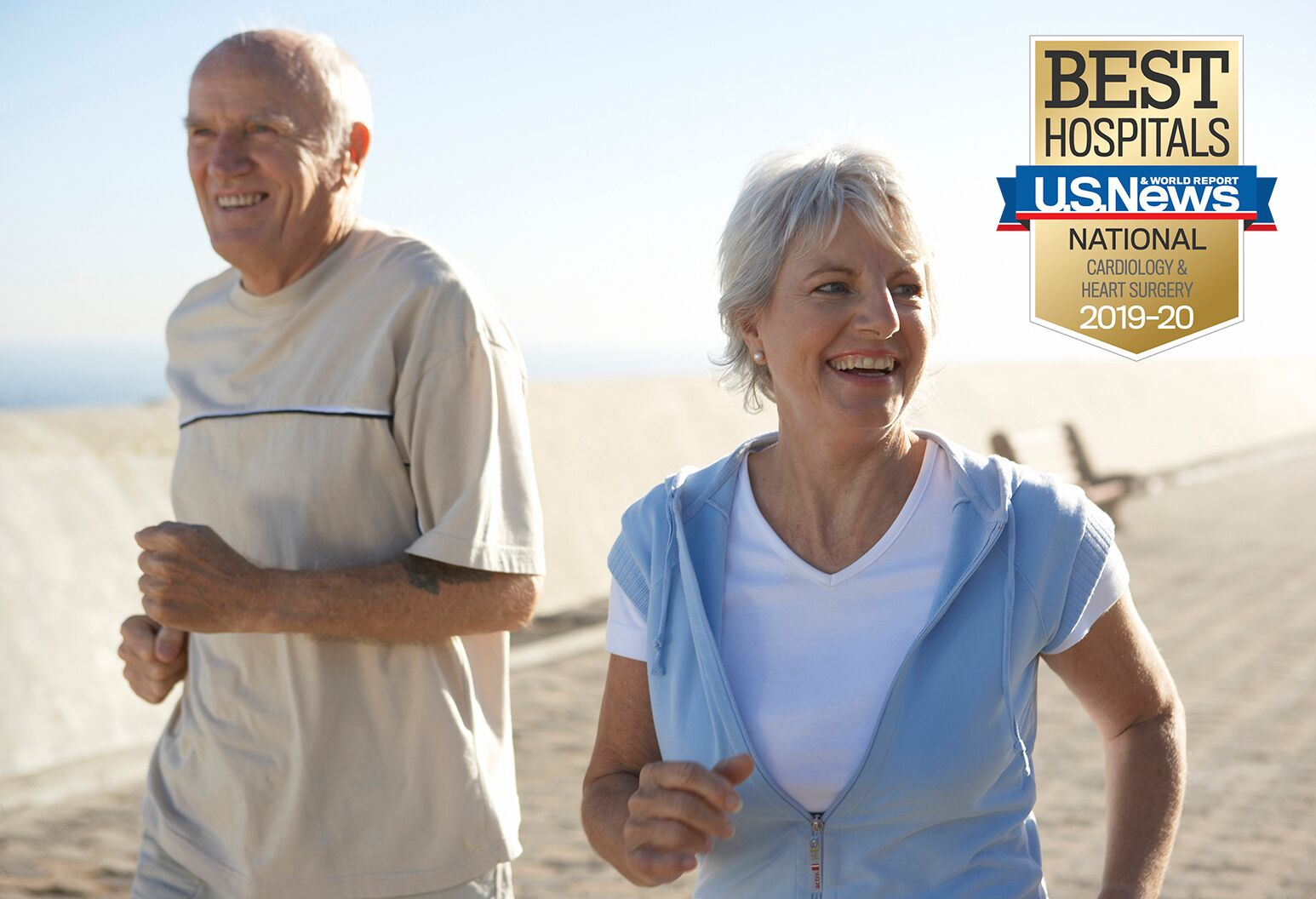 Older man and woman are smiling as they go for brisk walk along beach.