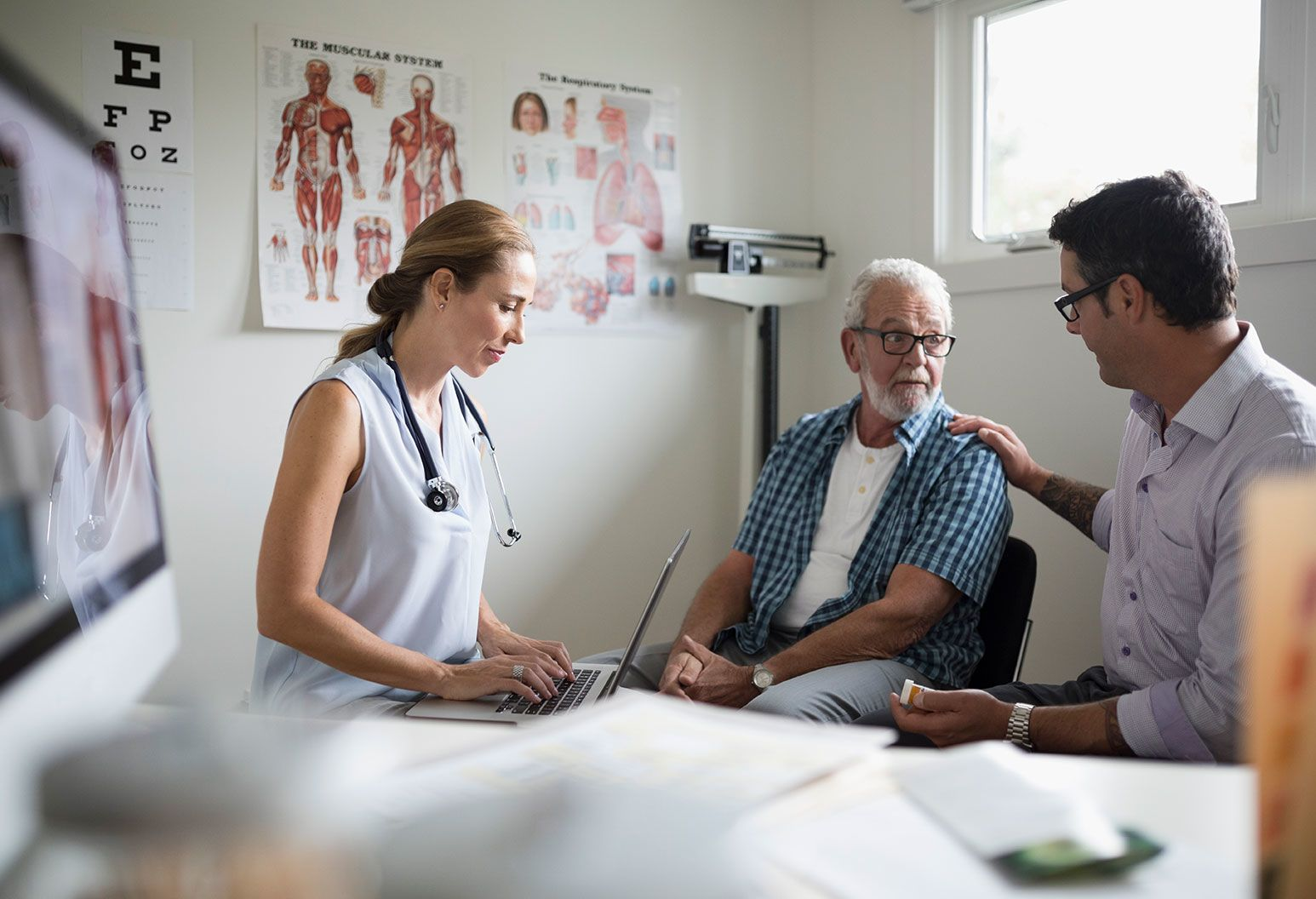 A female doctor sits with a laptop as she watches a comforting discussion between a n older man and a younger man. The men are both wearing similar glasses. They are all in a examination room filled with a medical scale, medical posters, and a cluttered d