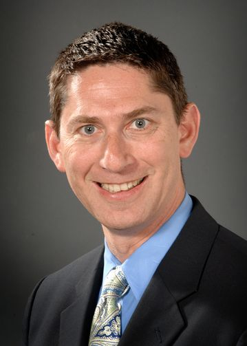 Bradley Sherman, MD, wearing a blue shirt and multi-colored tie