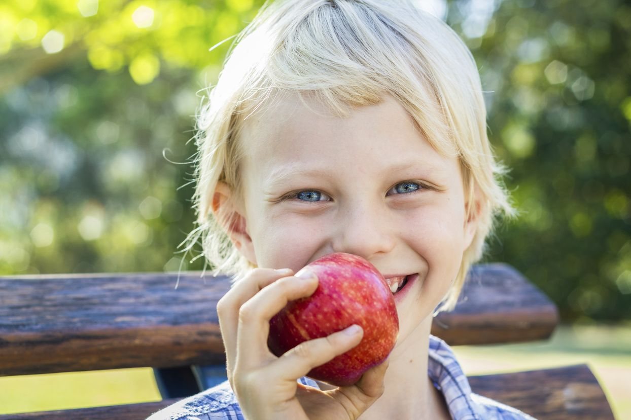 Child eating a red apple outdoors