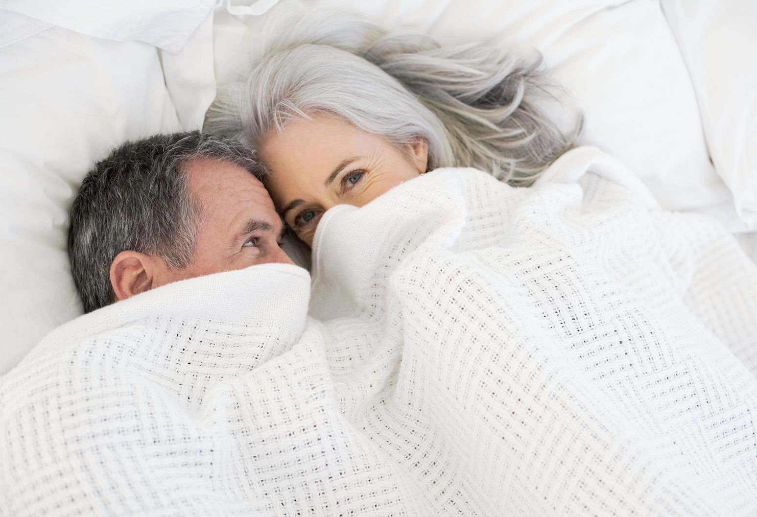 An older male and female with grey hair are smiling as they lay together under a blanket covering their mouths. The older male looks at the female adoringly as the female smiles at the camera.