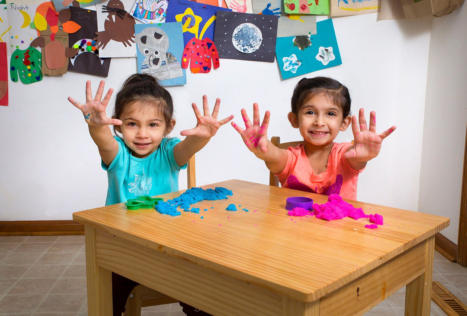Two young girls with dark hair playing with colorful Play-Doh.