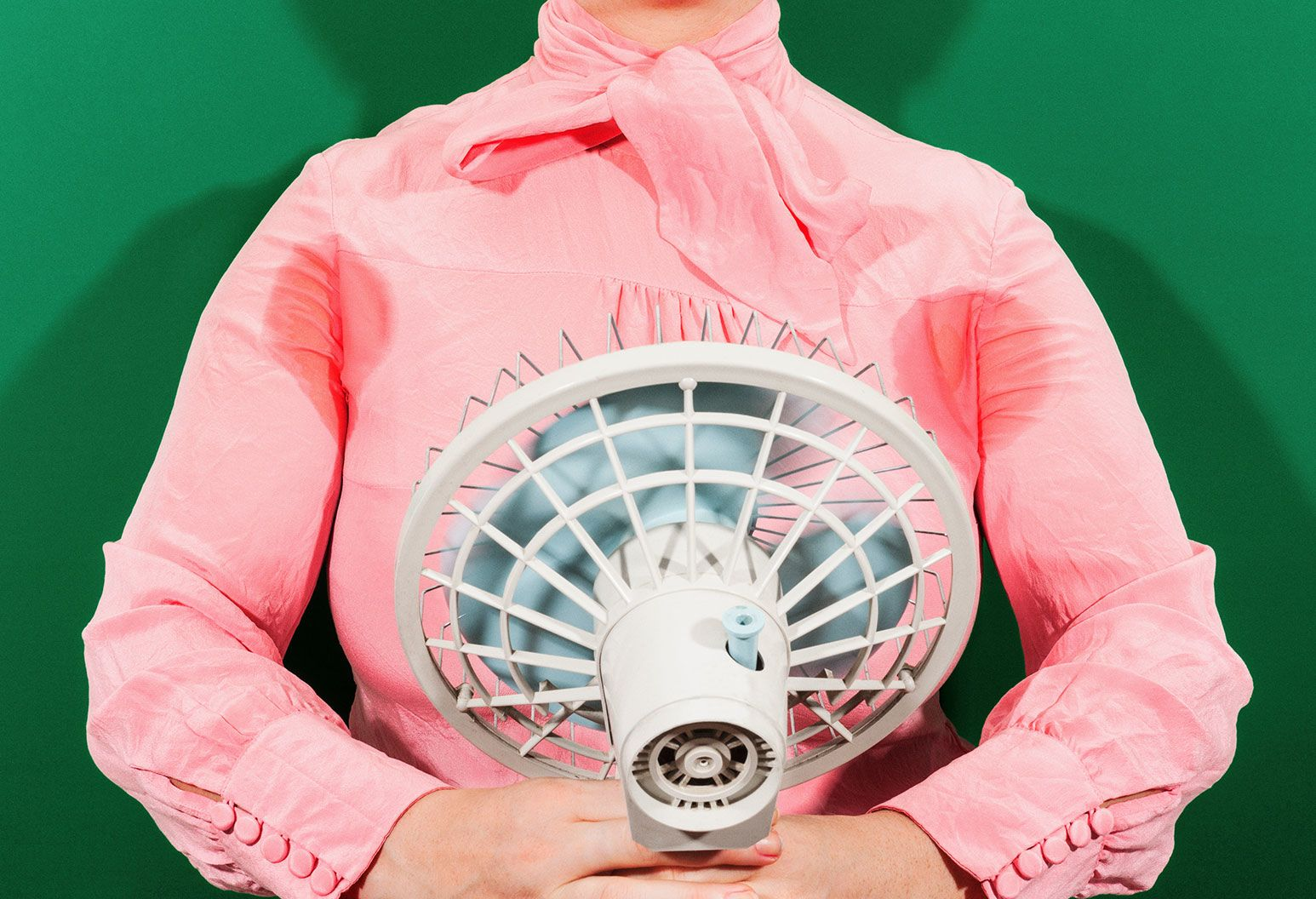 Woman in blink blouse holds up a fan to her chest. There are sweat stains under the armpits.