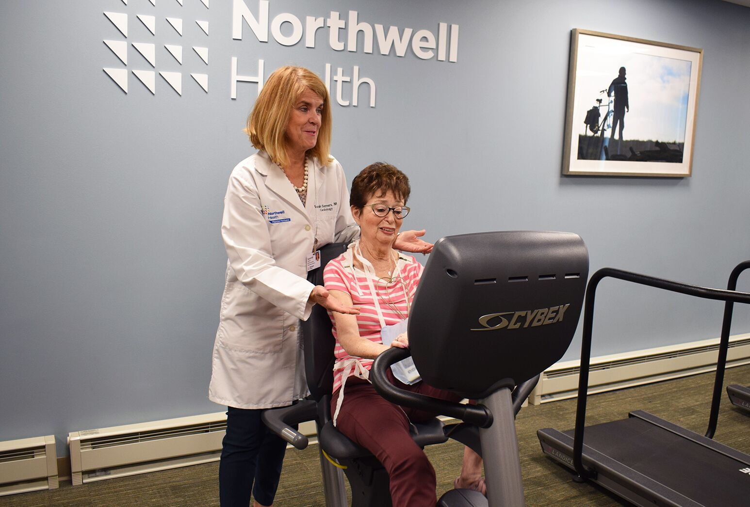 A Manhasset cardiac rehab patient exercises on the bike while her heart rate and rhythm is remotely monitored, as Sarah Siemers, NP, the program director, reviews the intensity of the workout.