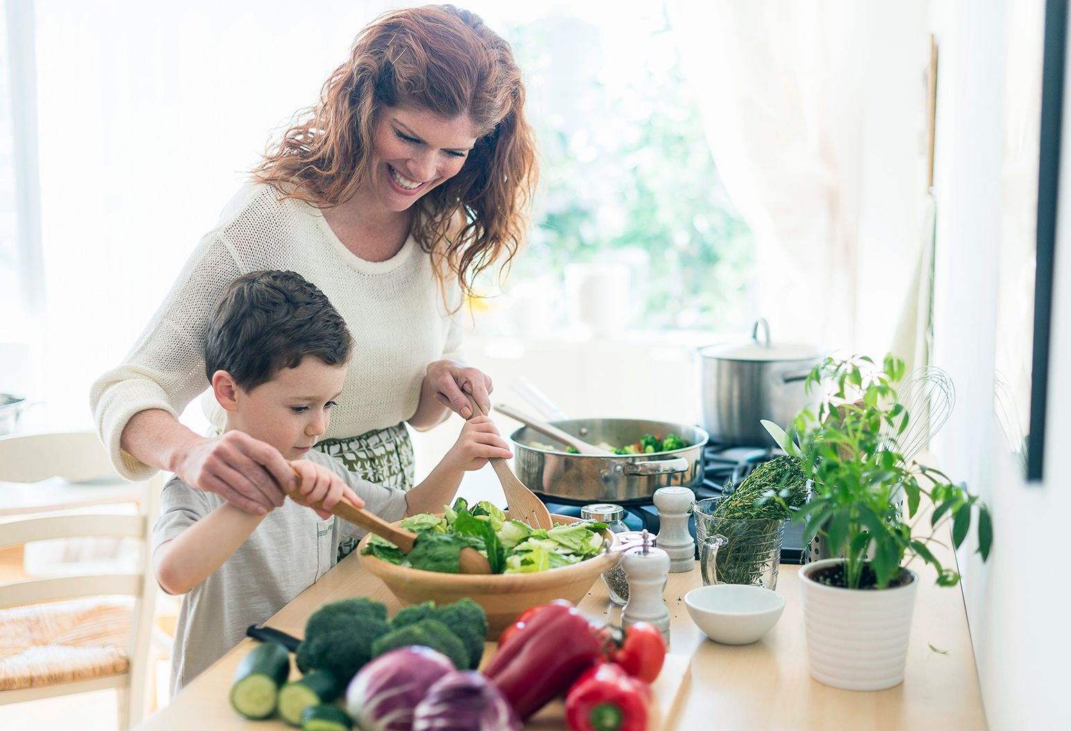 A young boy and his mother are in a kitchen making a salad together. There is something cooking on the stove and vegetables on a butting board.