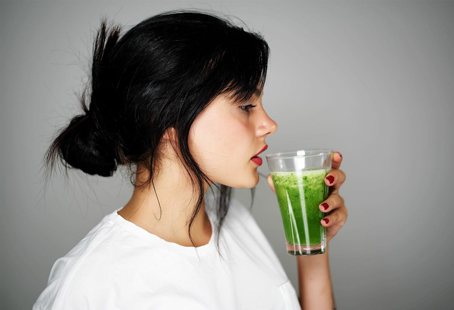 A young woman with long black hair tied up in a white tshirt holds a glass of green fluid close to her lips.